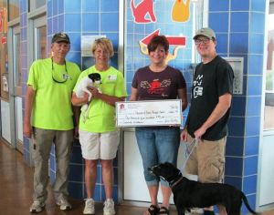 Laurie Loew gives Friends of Austin Animal Center donation.